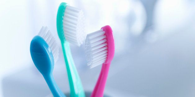Three toothbrushes, blue, green, pink